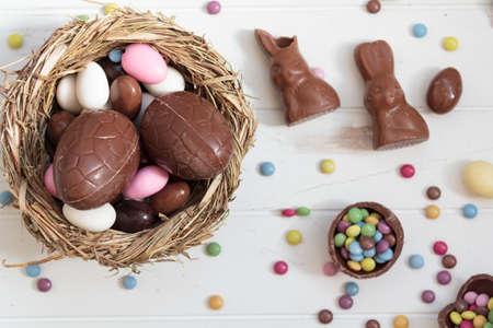 Top view of chocolate eggs and easter almonds, chocolate rabbits and other sweets on white wooden table