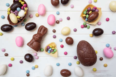 Top view of large variety of easter sweets, chocolate eggs, chocolate bunny, sweet almonds and other candies on white wooden table