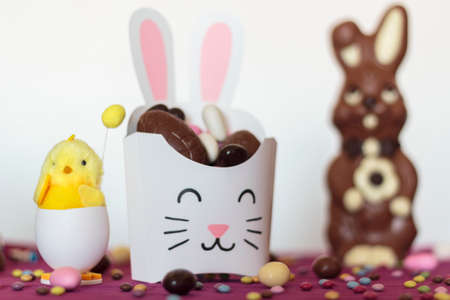 Party treat box with edible easter eggs, decorative chick and chocolate bunny on decorated table