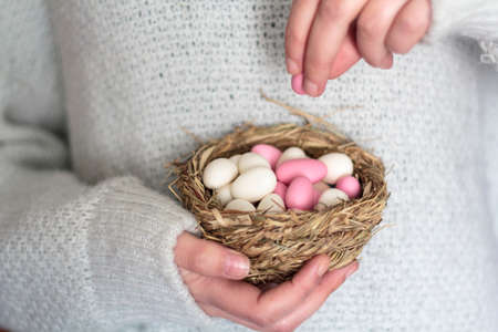 Woman hands holding bird nest with sugared Easter eggs Reklamní fotografie