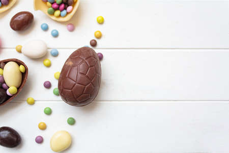 Top view of chocolate eggs and easter sweets on white wooden table with copy space