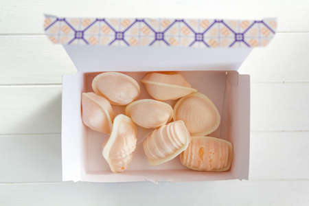 Top view of box with traditional portuguese sweet called Ovos Moles de Aveiro in white wooden table