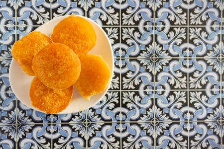 Top view of portuguese sweet bean tarts called Pastel de Feijao on portuguese tiles background Reklamní fotografie