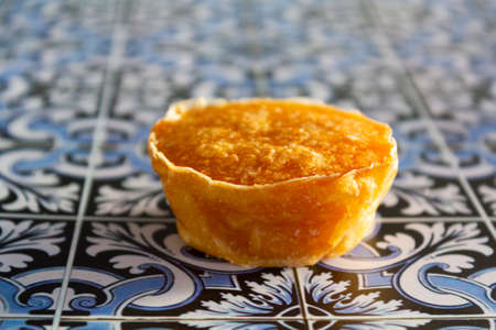 Traditional portuguese sweet bean pastry called Pastel de Feijao on portuguese tiles background