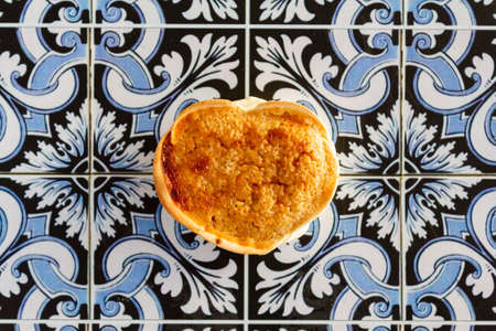 Top view of portuguese cheesecake called Queijada de Sintra on portuguese tiles background