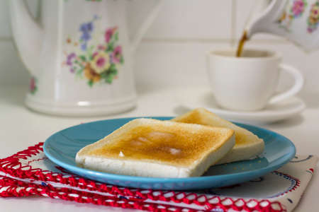 Breakfast table with butter toast and black coffee