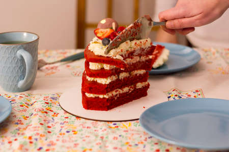 Hand cutting a slice of Red velvet layer cake