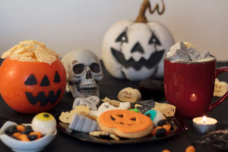Halloween party table with treats, hot drink and snacks