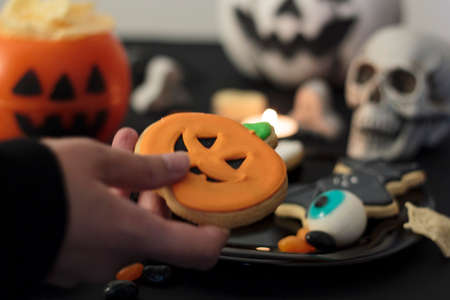 Woman holding a halloween cookie from festive table