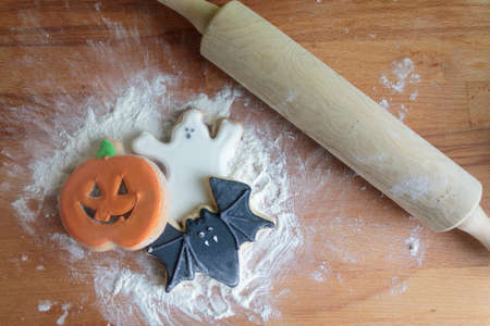 Top view of Halloween cookies on wooden board with flour and rolling pin Standard-Bild