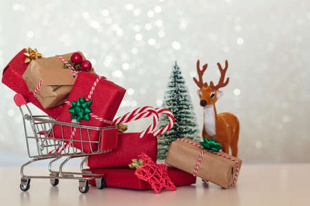 Christmas presents on shopping cart with christmas tree and reindeer