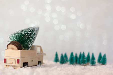 Rear view of truck with christmas tree on snowy background with copy space