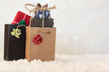 Shopping bags with wrapped christmas gifts inside on snow with blurred background wih copy space Standard-Bild