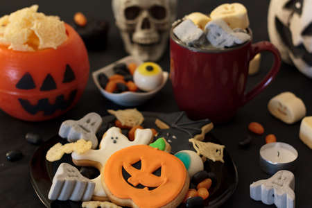 Halloween party table with snacks, cookies, treats, hot drink and halloween decoration Standard-Bild