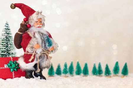Santa Claus with christmas gift and christmas trees on snow. Blurred shiny background with copy space