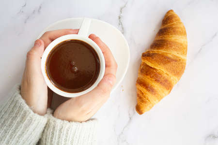 Top view of woman hands holding cup with hot chocolate drink and french croissant on marble table