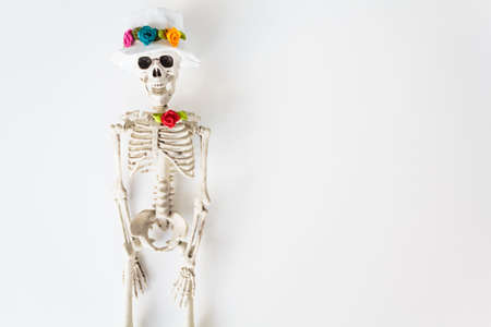 Skeleton with hat and colorful flowers on white background with copy space. Halloween and Dia de los muertos concept