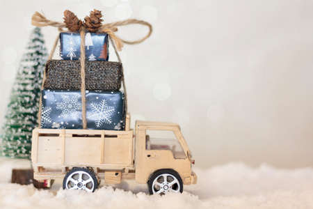Christmas truck with christmas gifts on snowy road with christmas tree on the background Standard-Bild