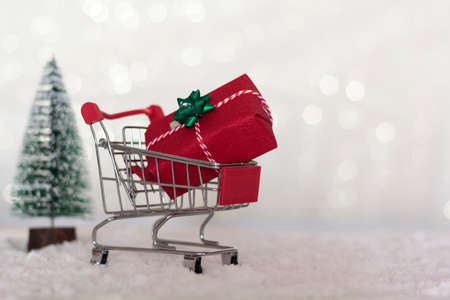 Shopping cart with christmas gift and christmas tree on snowy background with copy space