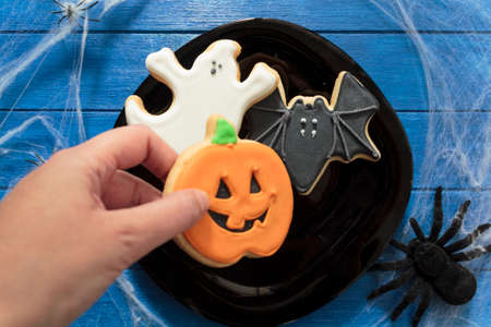 Top view of woman's hand holding halloween cookie