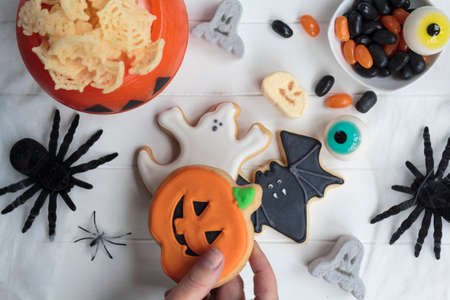 Woman hand holding halloween cookie from festive table with other candy and snacks