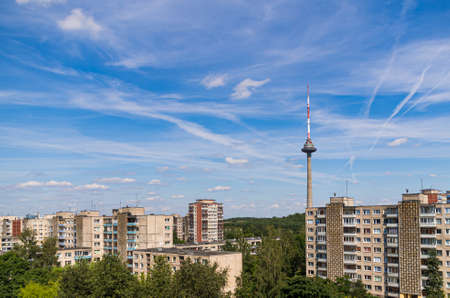 Shots towards Vilnius TV tower in the capital of Lithuania. A view from high above. Soviet built residential block buildings seen in the surroundings with a bright blue sky as a background.