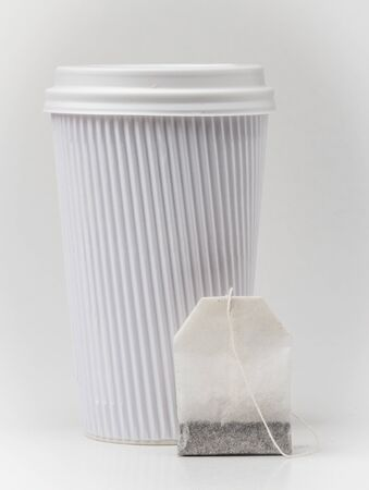 teabag: White ribbed paper cup and a teabag on white background Stock Photo