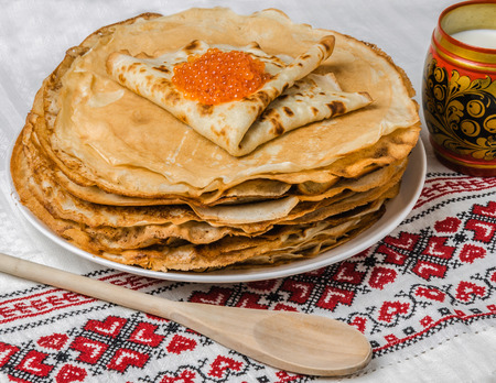 Pancakes with salmon caviar traditional Russian meal on cross stiched table cloth photo
