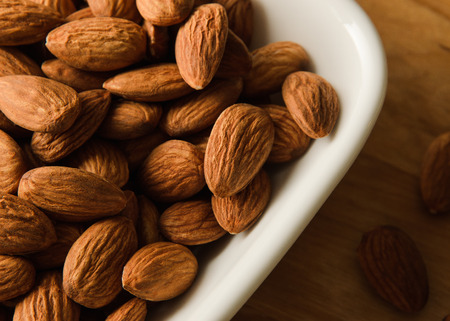 frutas secas: Healthy snack whole almond nut kernels in white bowl Foto de archivo