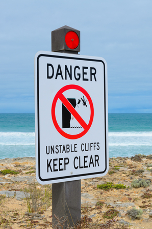 steep cliff sign: Warning sign danger unstable cliffs keep clear rural coast line Stock Photo