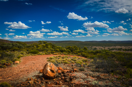 red soil: Curvy red soil dirt road Australian outback rural wilderness scene Stock Photo