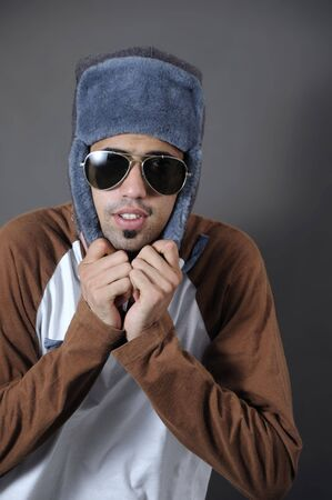 Portrait of young trendy guy in sunglasses and winter hat