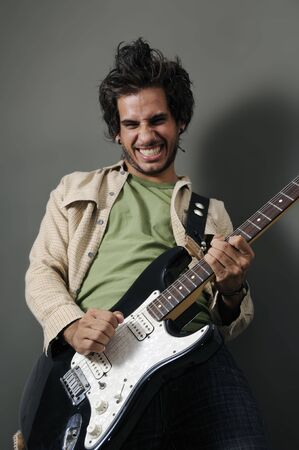 instrumentalist: Portrait of young guitarrist with funny expression