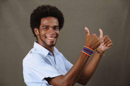 Portrait of joung friendly african american man with thumbs up