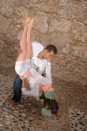 Portrait of young hispanic couple dancing against stone background photo