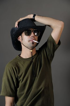 Portrait of young male smoking with sunglasses and cowboy hat Stock Photo