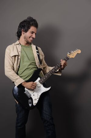 instrumentalist: Portrait of young handsome musician playing electric guitar
