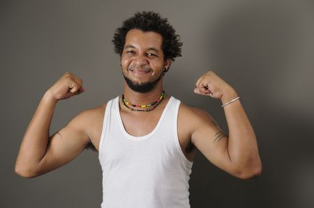 Portrait of young happy latino man showing his strong muscles photo