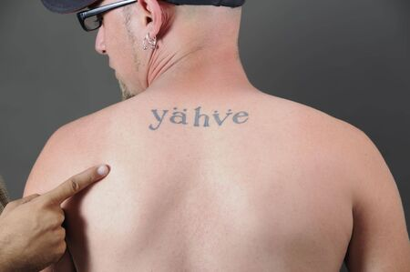 credo: Portrait of young adult back with religious tattoo and the word  Stock Photo