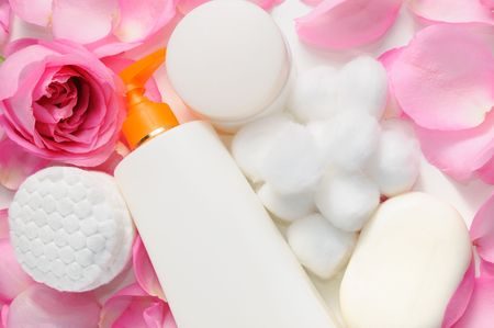 Skin care products with rose petals and cotton swabs