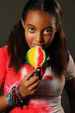 Portrait of young african girl eating a lollipop with happy expression Stock Photo - 3478324