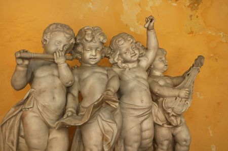 erode: Statue of 4 little angels playing musical instruments against yellow wall - Old Havana Stock Photo