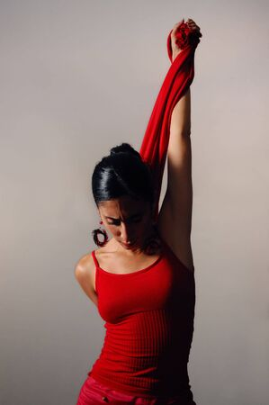 Artistic portrait of young hispanic dancer woman in red clothes photo
