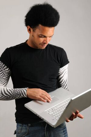 Portrait of young trendy latino man holding modern laptop computer photo