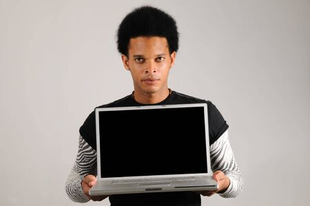 Portrait of young trendy latino man holding modern laptop computer Stock Photo - 3686615