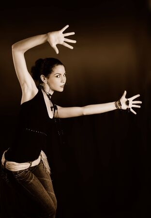 Portrait of young fashion female posing with hands up photo