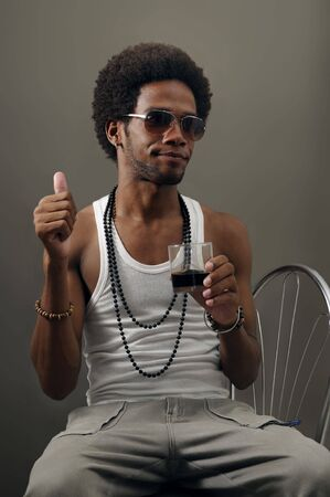 Portrait of young trendy latino man drinking with attitude photo
