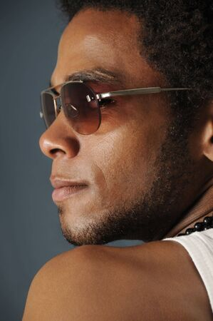 Profile Portrait of young african man wearing sunglasses photo