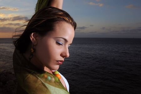 Portrait of young fashion female model relaxing by the ocean at sunset photo