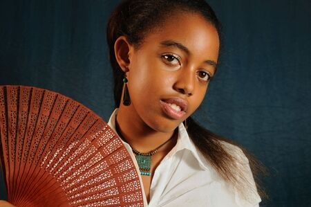 Portrait of young african fashion teenage female with fan photo